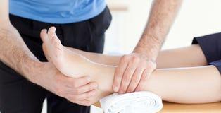 Ciérrese para arriba de un fisio haciendo un masaje del pie Fotos de archivo libres de regalías