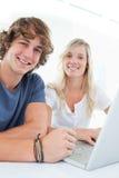 Ciérrese para arriba de un par sonriente con una computadora portátil Imágenes de archivo libres de regalías