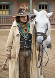 Ciérrese para arriba de un vaquero que se coloca al lado de su caballo Foto de archivo libre de regalías