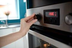Ciérrese para arriba del control de la temperatura del ajuste de la mano de la mujer en el horno Fotos de archivo libres de regalías