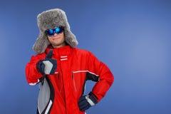 Ciérrese para arriba del hombre confiado que se coloca en sombrero y capa del invierno. Fotografía de archivo