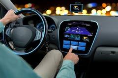 Ciérrese para arriba del hombre que conduce el coche con el sistema de navegación Fotos de archivo libres de regalías