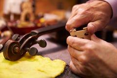 Ciérrese para arriba del hombre que restaura el violín en taller Foto de archivo