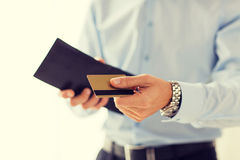 Ciérrese para arriba del hombre que sostiene la cartera y la tarjeta de crédito Foto de archivo libre de regalías