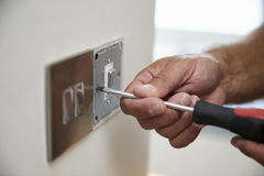 Ciérrese para arriba del interruptor de Repairing Domestic Light del electricista Foto de archivo libre de regalías