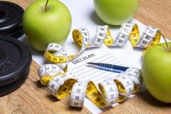 Ciérrese para arriba del papel con plan, las manzanas, las pesas de gimnasia y medida de la dieta Fotografía de archivo