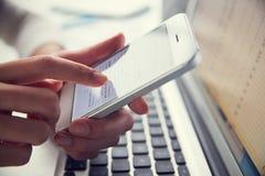 Ciérrese para arriba del teléfono de Person At Laptop Using Mobile Imagenes de archivo