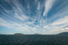 Cirrus clouds above the water. Strands of cirrus clouds above the water royalty free stock photos