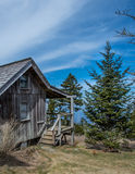 Cirrus Clouds Above Weathered Cabin. In mountains stock images