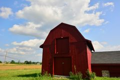 Cirrus clouds exploding from the top of a little red barn in Hollis, NH. Clouds project from the top of a small red barn with annex In the distance you see trees Royalty Free Stock Image