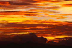 Cirrus clouds orange yellow sunset. Bright orange and yellow sunset sky filled with cirrus and cirrocumulus clouds stock image