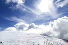 Big cloud in the sky. Cirrus and cumulus clouds over snowed mountains at the pyrenees Stock Images
