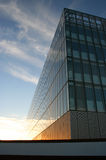 Cirrus glass. Glass faced building below cirrus clouds at sunset royalty free stock photo