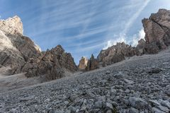 Cirrus over rocky pinnacles at the foot of Tofana southern wall. Cortina d`Ampezzo, Italy stock photos