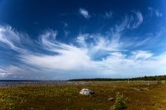 Cirrusmolnmoln över stranden och havet av norden Arkivbild