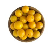 Ciruelos amarillos en un cuenco de madera aislado en el fondo blanco Foto de archivo libre de regalías