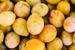 Ciruelos amarillos frescos Frutas maduras en una caja de madera en jard?n del verano foto de archivo