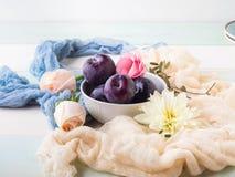 Ciruelos azules en cuenco con las flores Imagen de archivo