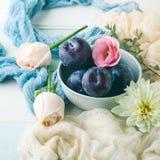 Ciruelos azules en cuenco con las flores Foto de archivo