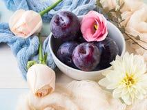 Ciruelos azules en cuenco con las flores Imagen de archivo libre de regalías