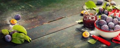 Ciruelos y tarro de atasco en la tabla imagen de archivo libre de regalías