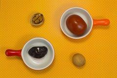 Ciruelos y tomates conservados en vinagre en un fondo amarillo aún Fotos de archivo libres de regalías