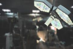 Cirugía en el cuarto oscuro bajo luz de la lámpara shadowless foto de archivo libre de regalías