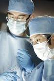 Cirujano asiático que trabaja con el ayudante en cirugía Imagenes de archivo