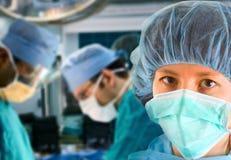 Cirujano de sexo femenino con las personas quirúrgicas Imagenes de archivo