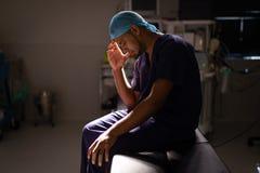 Cirujano de sexo masculino nervioso que sienta el sitio en funcionamiento en el hospital foto de archivo libre de regalías