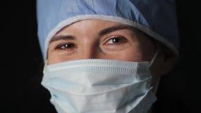Cirujano que pone en un cierre de la máscara metrajes