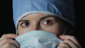 Cirujano que pone en un cierre de la máscara almacen de video