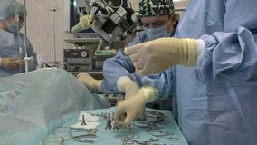 Cirujanos en la sala de operaciones realizar cirugía microscópica en órganos ENT usando un microscopio quirúrgico y los instrumen almacen de metraje de vídeo