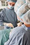 Cirujanos que funcionan en paciente imagen de archivo libre de regalías