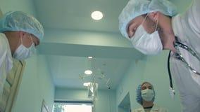 Cirujanos que miran abajo el paciente que consigue listo para la cirugía urgente almacen de metraje de vídeo