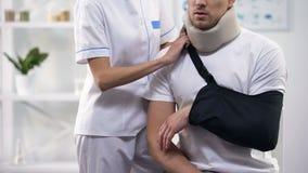 Cirurgião fêmea que ajusta o estilingue paciente masculino do braço, a ortopedia e o período da reabilitação filme