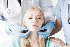 Cirurgião plástico ou doutor com paciente imagem de stock royalty free