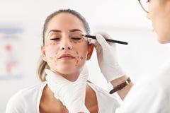 Cirurgião plástico que faz marcas no corpo do paciente fotos de stock