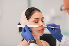 Cirurgião plástico que veste as luvas azuis que fazem medidas da cara imagem de stock
