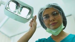 Cirurgião que ajusta a iluminação antes da operação, cirurgia plástica, cosmetologia vídeos de arquivo