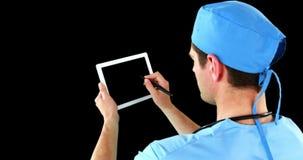 Cirurgião que usa a tabuleta digital filme