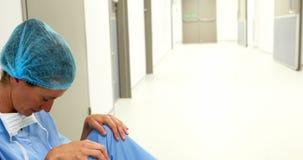 Cirurgião triste que senta-se no assoalho no corredor video estoque