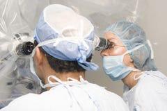 Cirurgiões fêmeas e masculinos que usam o funcionamento imagens de stock