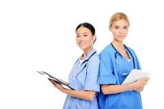 cirurgiões multi-étnicos fêmeas com prancheta e a tabuleta digital, imagem de stock