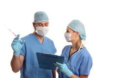 Cirurgiões que consultam a fala sobre informes médicos imagem de stock