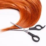 Cisaillements rouges brillants de cheveux et de coupe de cheveux Photographie stock libre de droits
