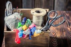 Ciseaux, aiguille et fils dans la boîte en bois Photographie stock