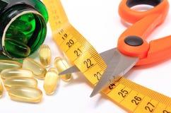 Ciseaux avec le ruban métrique et pilules médicales sur le blanc Image libre de droits