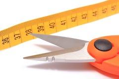 Ciseaux avec le ruban métrique sur le fond blanc Photo stock