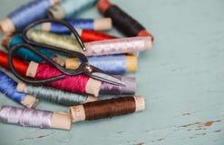 Ciseaux avec les fils en soie pour broder sur le fond de vintage Photographie stock